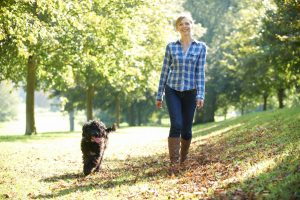 Woman walking her dog in fall